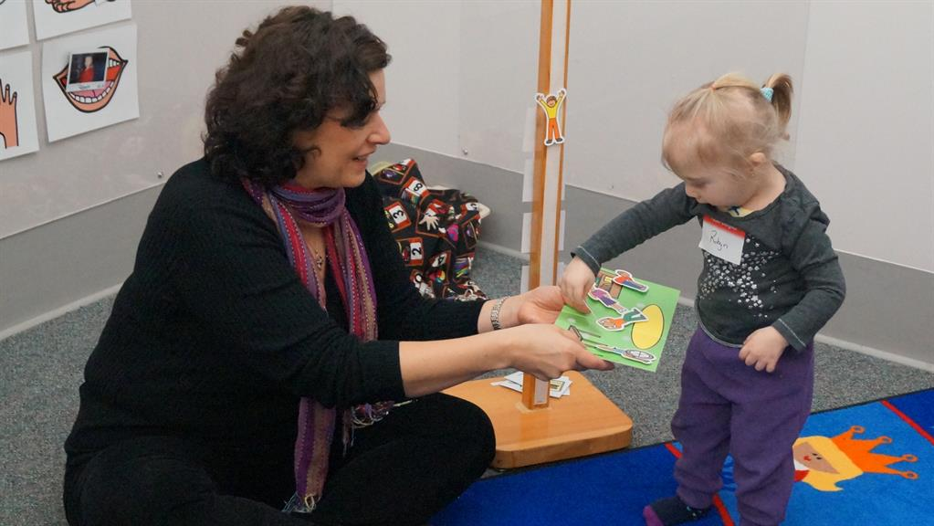 Norma Williams, a KidsAbility Speech-Language Pathologist, sits cross legged on the floor in a KidsAbility therapy room. Behind her on the wall are symbols to help encourage speech and she is pictured showing a young client a book.