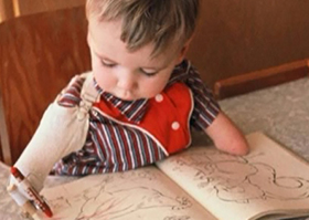 A young boy is learning how to colour with a crayon using his prosthetic arms.